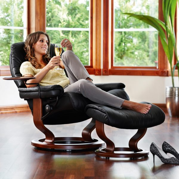 Stressless Sunrise Classic Recliner and Ottoman in Paloma Black with a Walnut Base, Swing Table and a Reclined Lady